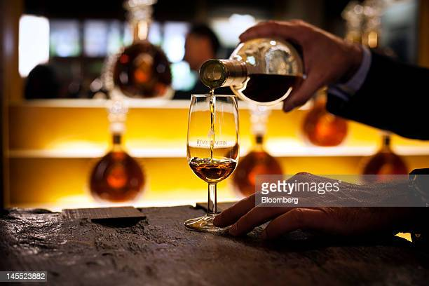 An employee pours cognac into a glass from a bottle of Remy Martin VSOP Mature Cask Finish Cognac at the Remy Cointreau SA headquarters in Cognac...