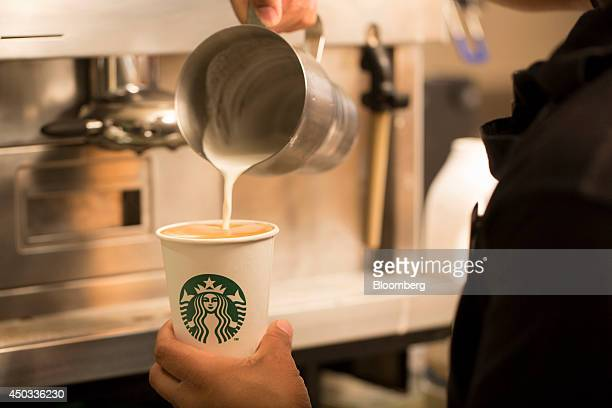 An employee pours milk into a cardboard coffee cup inside a Starbucks Corp coffee shop in London UK on Monday June 9 2014 UK services companies'...