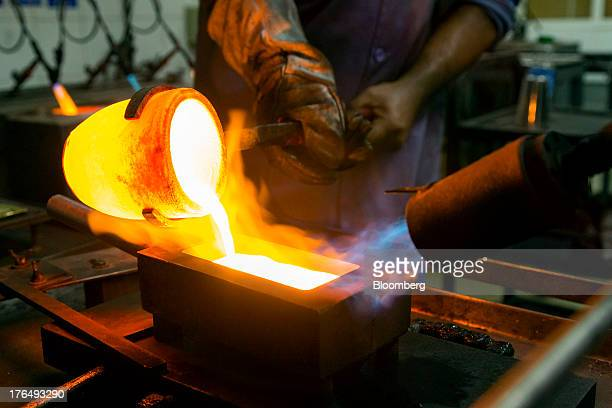 An employee pours molten gold from a crucible into a one kilogram mould after refining at the Kaloti Jewellery LLC factory in Sharjah United Arab...