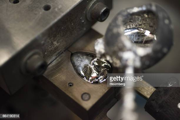 An employee pours molten metal into a pommel mold at the WR Case Sons Cutlery Co manufacturing facility in Bradford Pennsylvania US on Wednesday...