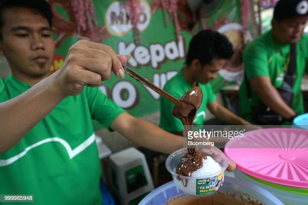 An employee pours molten milo chocolate over a bowl of crushed ice while preparing an order of Milo on round ice snack at an Es KepalMiloViral...