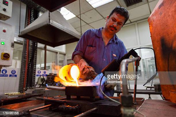 An employee pours one kilogram of molten gold into a heated mould after refining at the Kaloti Jewellery LLC factory in Sharjah United Arab Emirates...