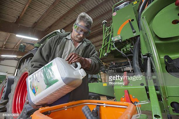 An employee pours Skyway fungicide into the tank of a Amazone UX 5200 field sprayer vehicle at the Bayer CropScience test farm operated by Bayer AG...