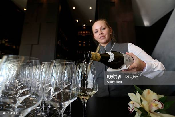 An employee pours white wine into glasses ahead of an event at the InterContinental Hotel Davos operated by InterContinental Hotels Group Plc ahead...