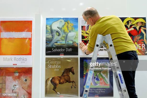 An employee prepare calender at an exhibitor's stand prior to the opening of the Frankfurt Book Fair on October 9, 2018 in Frankfurt, Germany....