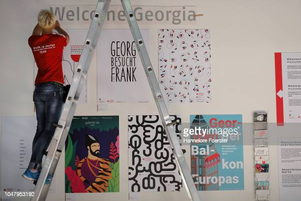 An employee prepare poster of Georgia, the Guest of Honour, at an exhibitor's stand prior to the opening of the Frankfurt Book Fair on October 9,...