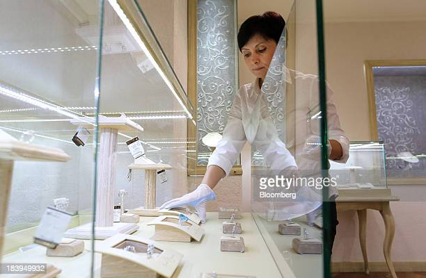 An employee prepares a glass display case containing diamond jewelry for sale inside a luxury jewelry store operated by Kristall Production Corp in...