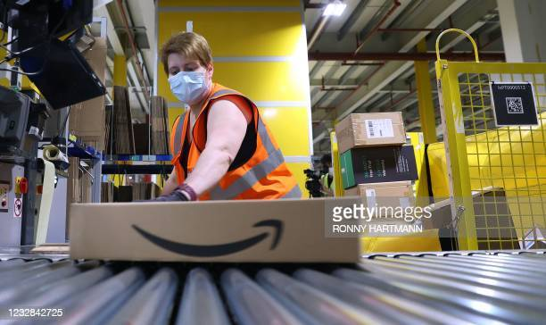 An employee prepares a package for shipment at the Amazon logistics centre in Suelzetal near Magdeburg, eastern Germany, on Mai 12, 2021. - The US...