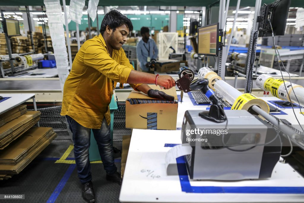 An employee prepares a package for shipment at the Amazon.com Inc. fulfillment center in Hyderabad, India on Thursday, Sept. 7, 2017. Amazon opened its largest Indian fulfillment center in Hyderabad. The center spans 400,000 square feet with 2.1m cubic feet of storage capacity the company said in a statement. Photographer: Dhiraj Singh/Bloomberg via Getty Images