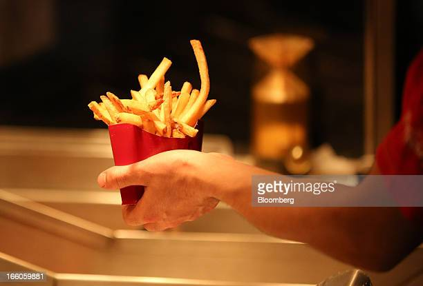 An employee prepares a portion of french fries for a customer in the kitchen area of a Wendy's fast food restaurant in Moscow Russia on Friday April...