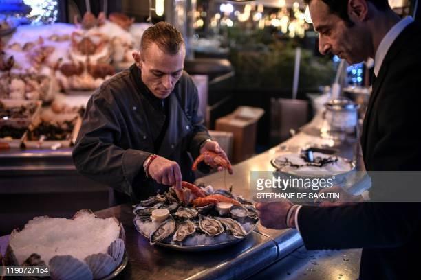 An employee prepares a sea food platter on December 29 2019 at an oyster bar in Paris