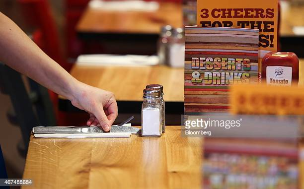 An employee prepares a table ahead of a lunch sitting inside a Pizza Hut restaurant owned by Yum Brands Inc at the company's flagship restaurant on...
