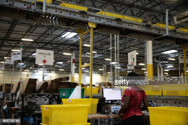 An employee prepares an online order at the Amazoncom Inc fulfillment center in Robbinsville New Jersey US on Thursday June 7 2018 Seattlebased...