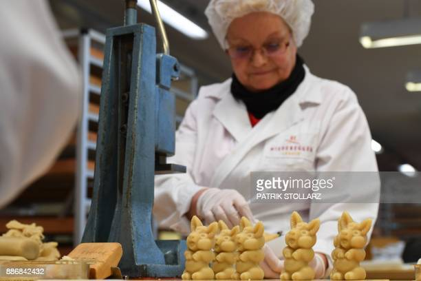 An employee prepares pigs made of fresh marzipan at the headquarters of the traditional confectionary maker JG Niederegger GmbH in Luebeck, Germany,...
