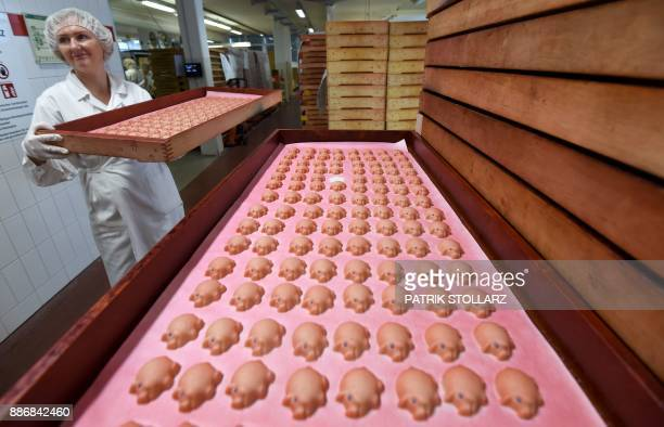 An employee prepares pigs made of fresh marzipan at the headquarters of the traditional confectionary maker JG Niederegger GmbH in Luebeck Germany on...