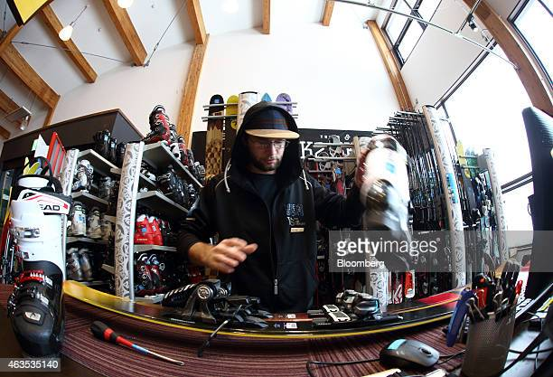 An employee prepares skis and boots in this photograph taken with a fisheye lens inside a rental ski shop at the Niseko Hanazono resort operated by...