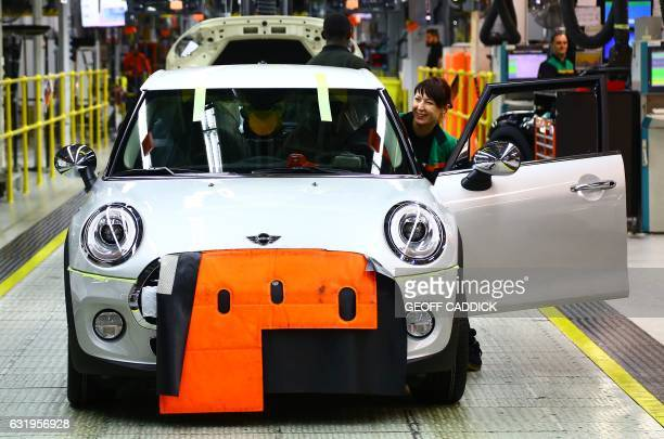An employee prepares to drive a completed Mini off the assembly line at the BMW Mini car production plant in Oxford west of London on January 17 2017...
