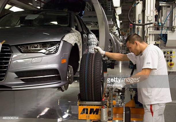 An employee prepares to fit a wheel to an Audi A7 automobile as it passes along the production line inside the Audi AG factory in Neckarsulm Germany...