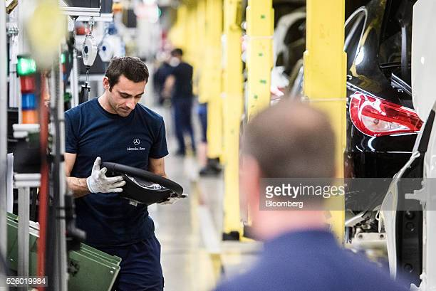An employee prepares to install a steering wheel on an automobile on the production line at the Mercedes-Benz AG automobile plant, operated by...