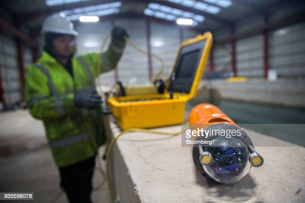 An employee prepares to lower the Aqua Vehicle Explorer for Insitu Sensing tethered miniremotely operated vehicle into the testing pool at Forth...