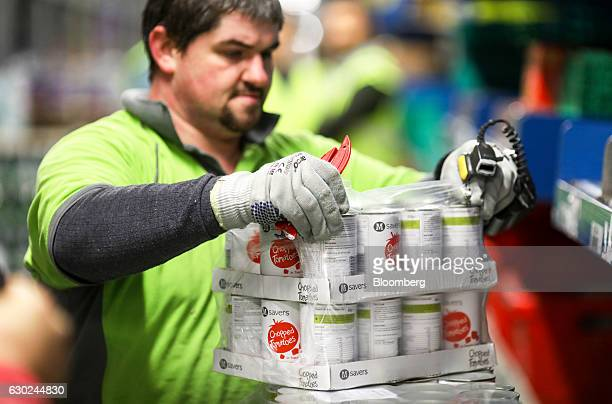 An employee prepares to place tins of tomatoes onto a conveyor belt at the Ocado Group Plc distribution centre in Dordon UK on Friday Dec 16 2016...