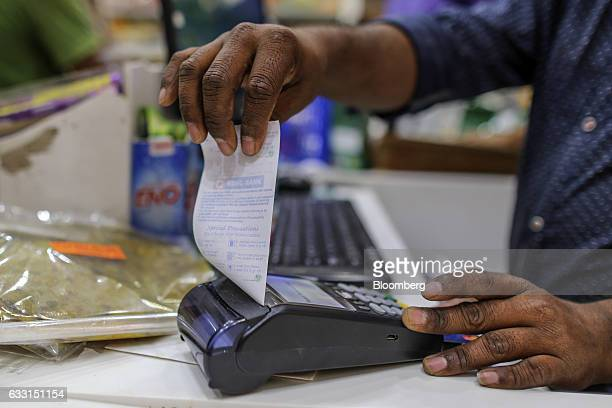 An employee prepares to tear off a receipt from a payment terminal at a supermarket in the Kurla area of Mumbai India on Saturday Jan 28 2017 India's...