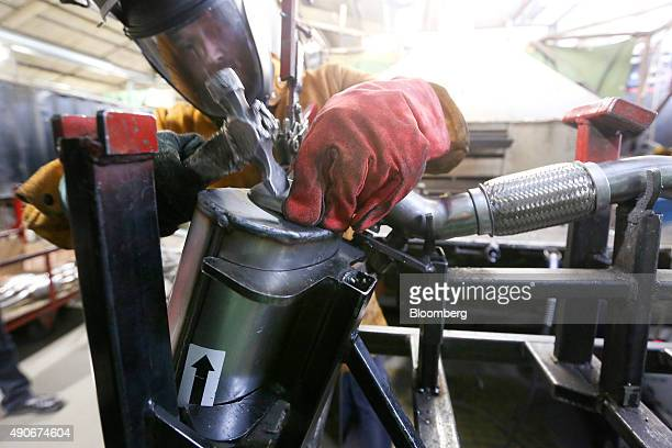 An employee prepares to weld parts on to a catalytic converter emission control devices for use in a Volkswagen AG automobile at BM Catalysts in...