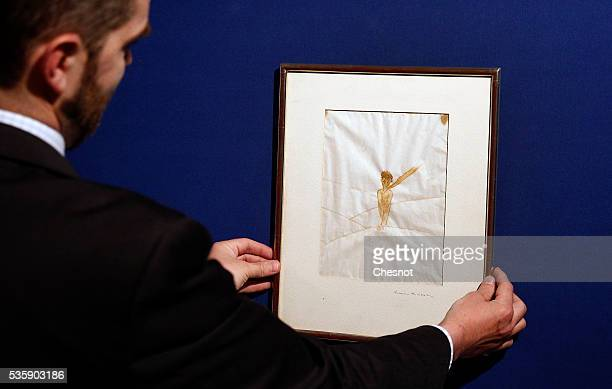 An employee presents a drawing from Antoine de SaintExupery that will be sold tomorrow by the auction house Artcurial on May 30 2016 in Paris France