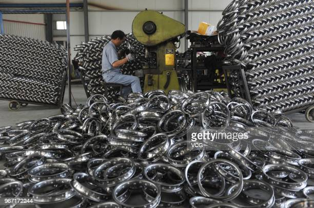 An employee processes steel rims for export at a sports equipment factory on June 4 2018 in Hangzhou China According to the data released by NBS...