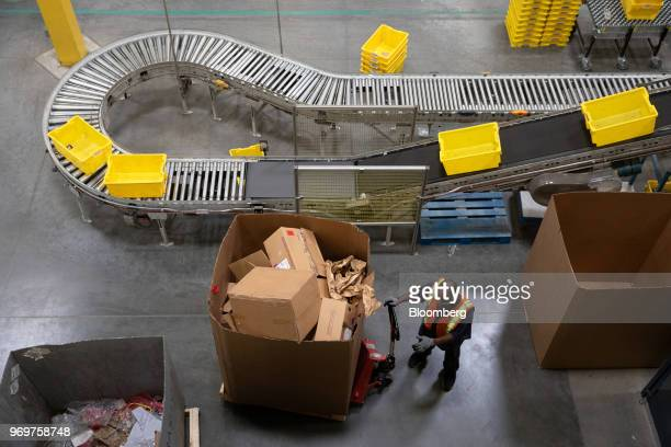 An employee pulls a cart full of discarded boxes at the Amazoncom Inc fulfillment center in Robbinsville New Jersey US on Thursday June 7 2018...