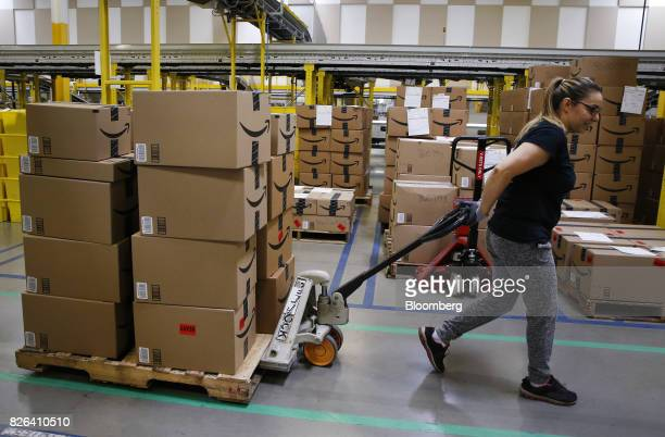An employee pulls a cart stacked with boxes at the Amazoncom fulfillment center in Kenosha Wisconsin US on Tuesday Aug 1 2017 Amazoncom Inc held a...