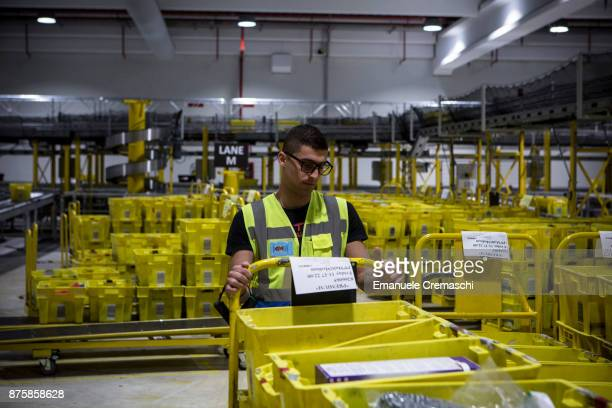An employee pulls a cart stacked with boxes at the Amazoncom MPX5 fulfillment center on November 17 2017 in Castel San Giovanni Italy Established in...