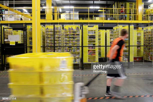 An employee pulls a pallet jack carrying plastic crates past goods in storage units at the Amazoncom Inc fulfillment center in Robbinsville New...