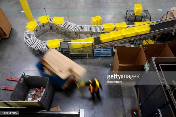 An employee pulls a pallet jack past plastic crates moving along a conveyor at the Amazoncom Inc fulfillment center in Robbinsville New Jersey US on...