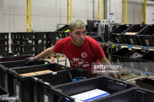 An employee pulls a stack of bins filled with inbound merchandise at the Amazoncom MPX5 fulfillment center on November 17 2017 in Castel San Giovanni...