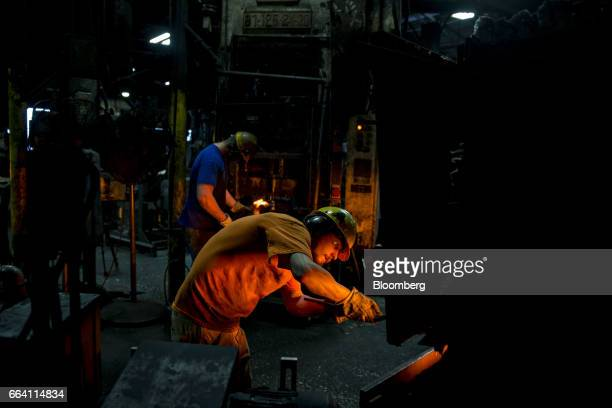 An employee pulls a steel billet from a furnace as tools are forged at the Vaughan Bushnell Manufacturing Co facility in Bushnell Illinois US on...