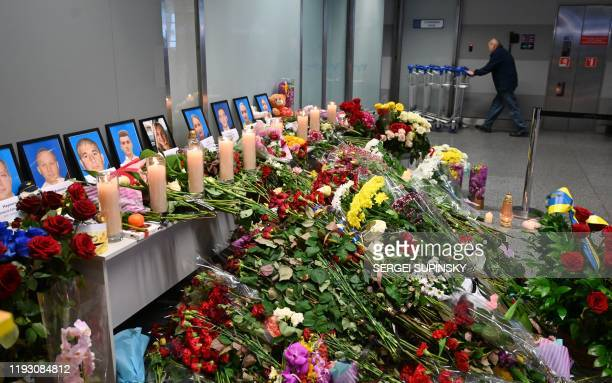 An employee pulls trolleys in background of a makeshift memorial set up for the victims of the Ukraine International Airlines Boeing 737800 that...
