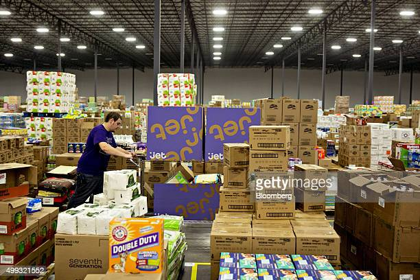 An employee pushes a cart of boxes while assembling customer orders at the Jetcom Inc fulfillment center on Cyber Monday in Kansas City Kansas US on...