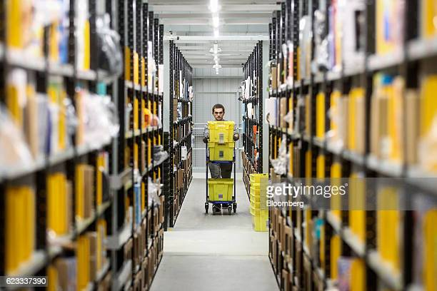 An employee pushes a cart past aisles of merchandise as he collects items for customers' delivery orders at an Amazoncom Inc fulfillment center in...