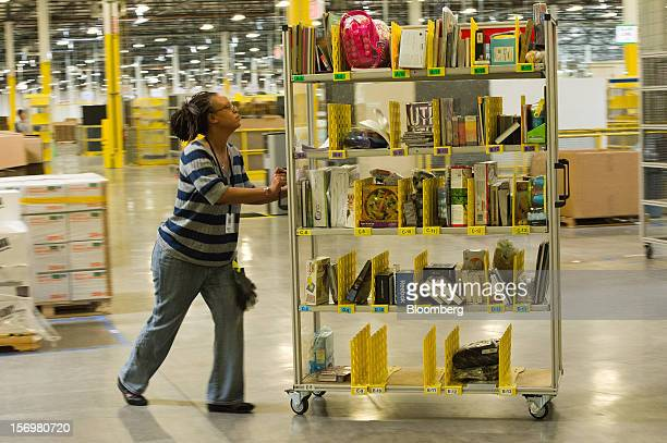 An employee pushes a cart with items to be shipped at the Amazoncom Inc distribution center in Phoenix Arizona US on Monday Nov 26 2012 US retailers...