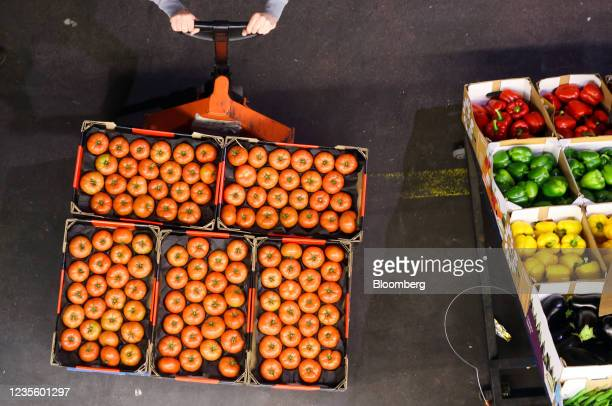An employee pushes a pallet of tomatoes in the Buyers Walk at New Covent Garden Market wholesale market in London, U.K., on Thursday, Sept. 30, 2021....