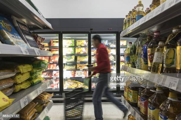 An employee pushes a shopping basket while fulfilling an electronic order in a WalMart Stores Inc miniwarehouse for the company's onehour delivery...