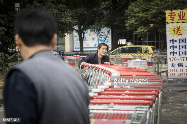 An employee pushes a string of shopping carts towards an RTMart hypermarket operated by Sun Art Retail Group Ltd in Shanghai China on Monday Nov 20...