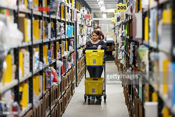 An employee pushes a trolley along an aisle at the Amazoncom Inc fulfillment center in Hemel Hempstead UK on Wednesday Nov 25 2015 WalMart and...