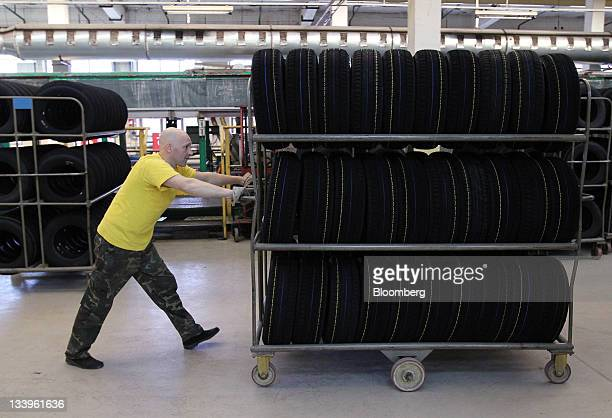 An employee pushes a trolley carrying completed car tires at the ZAO Sibur Holding tire manufacturing plant in Voronezh, Russia, on Friday, Nov. 18,...