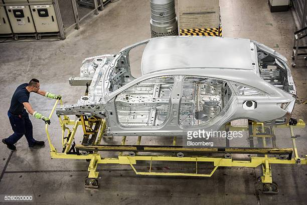 An employee pushes a trolley containing an automobile chassis inside the Mercedes-Benz AG automobile plant, operated by Daimler AG, in Kecskemet,...