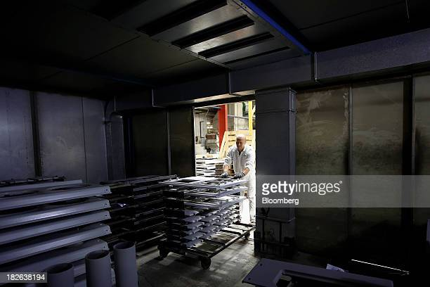 An employee pushes a trolley loaded with freshly primed doors and range cooker front panels produced by AGA Rangemaster Plc into a heat storage unit...