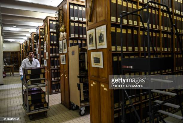 An employee pushes on a cart binders containing herbarium paper sheets to have the sheets digitalizated on March 12 2018 at the Claude Bernard LyonI...