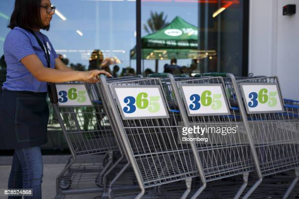 An employee pushes shopping carts during the grand opening of a Whole Foods Market 365 location in Santa Monica California US on Wednesday Aug 9 2017...