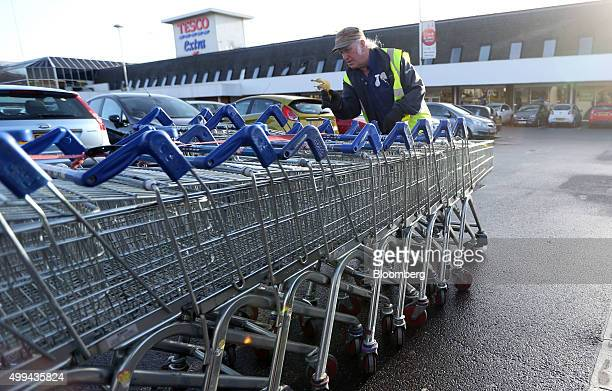 An employee pushes shopping trolleys back to the store at the Tesco Basildon Pitsea Extra supermarket operated by Tesco Plc in Basildon UK on Tuesday...